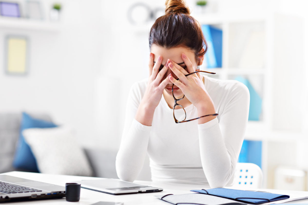 Lifestyle Habits that Can Affect Your Hormones; Picture showing young woman stressed while working in her home office
