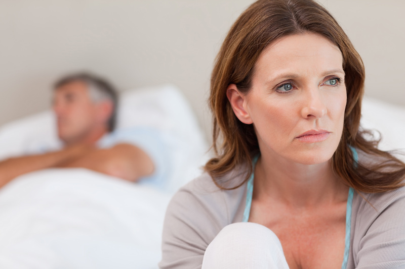 Sad mature woman on bed with her husband in the background; Blog: Is Menopause Keeping You Awake?