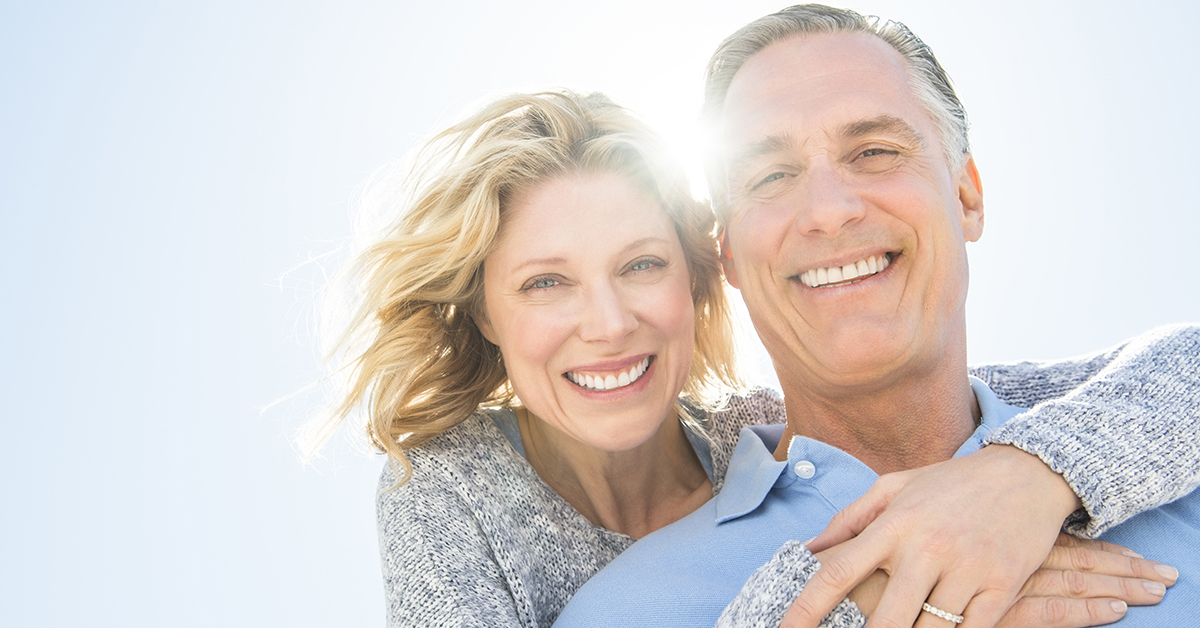 Low angle portrait of cheerful mature woman embracing man from behind against clear sky; blog: what is bioidentical hormone therapy?