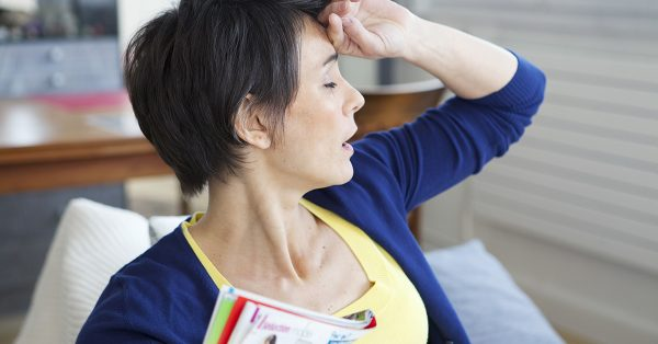 middle aged woman experiencing hot flashes; blog: how long does menopause last?