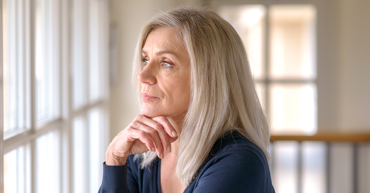 Attractive thoughtful woman with serious expression standing with her hand to her chin staring quietly out of a large window; blog: Can You Prevent Early Menopause?