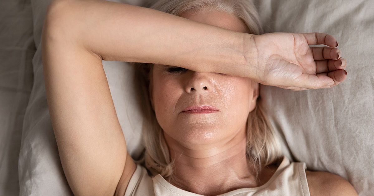 Close up top view middle-aged woman lying down in bed on pillow put hand on face, concept of female having insomnia sleeping disorder or migraine pain, melancholic mood, personal life troubles concept; blog: 15 Signs of Estrogen Dominance
