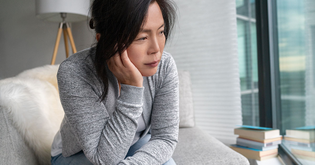 Sad Asian mature woman lonely at home self isolation quarantine for COVID-19 Coronavirus social distancing prevention. Mental health, anxiety depressed thinking senior chinese lady; blog: What's the Link Between Menopause and Depression?