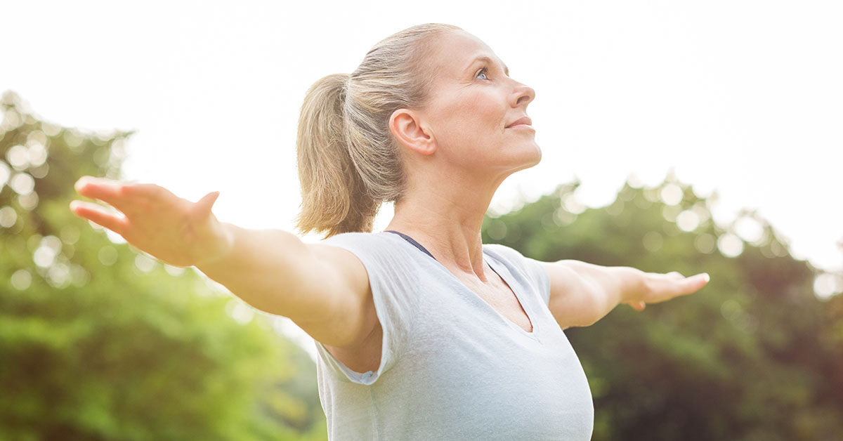 Mature woman doing yoga at park and looking away. Senior blonde woman enjoying nature during a breathing exercise. Portrait of a fitness woman stretching arms and looking away outdoor; blog: 8 Ways to Practice Self-Care During Menopause