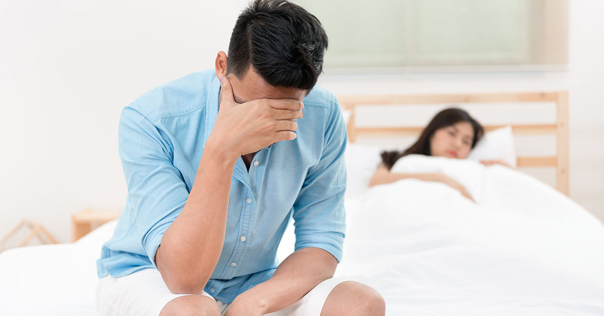 Husband unhappy and disappointed in the erectile dysfunction during sex while his wife sleeping on the bed. Sexual Problems in Men; blog: 10 Low T Symptoms & How to Treat Them