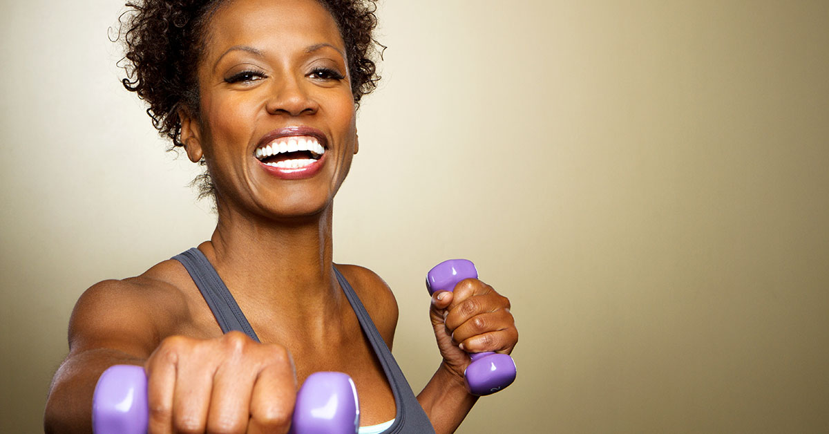 Happy African American fitness woman lifting dumbbells smiling a; blog: 12 Exercises to Improve Bone Health