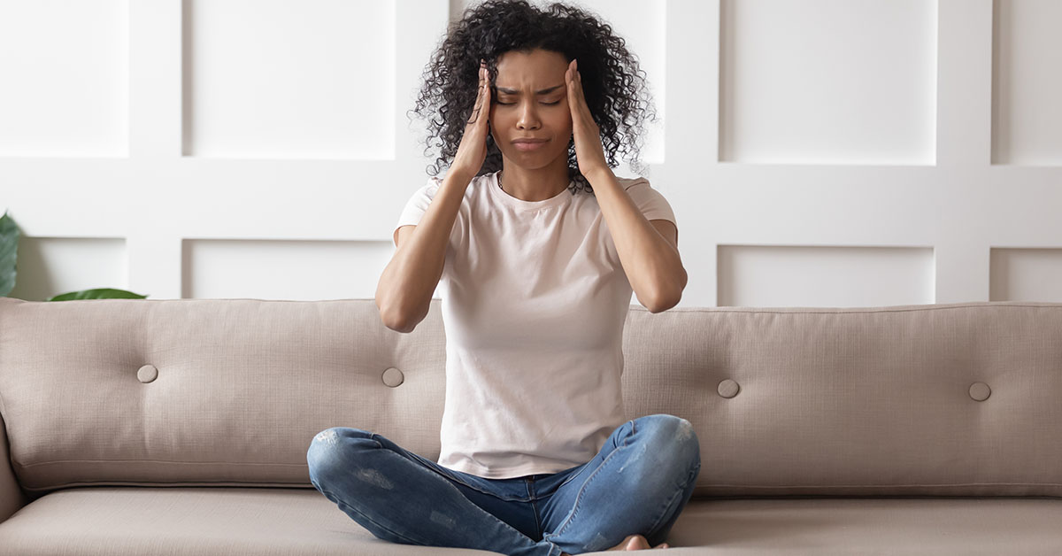 Upset stressed young african woman massage temples feel strong headache concept, frustrated tired black girl touching aching head suffer from migraine high blood pressure sitting on sofa at home; blog: 10 Causes of Hormone Imbalance (Other than Menopause)