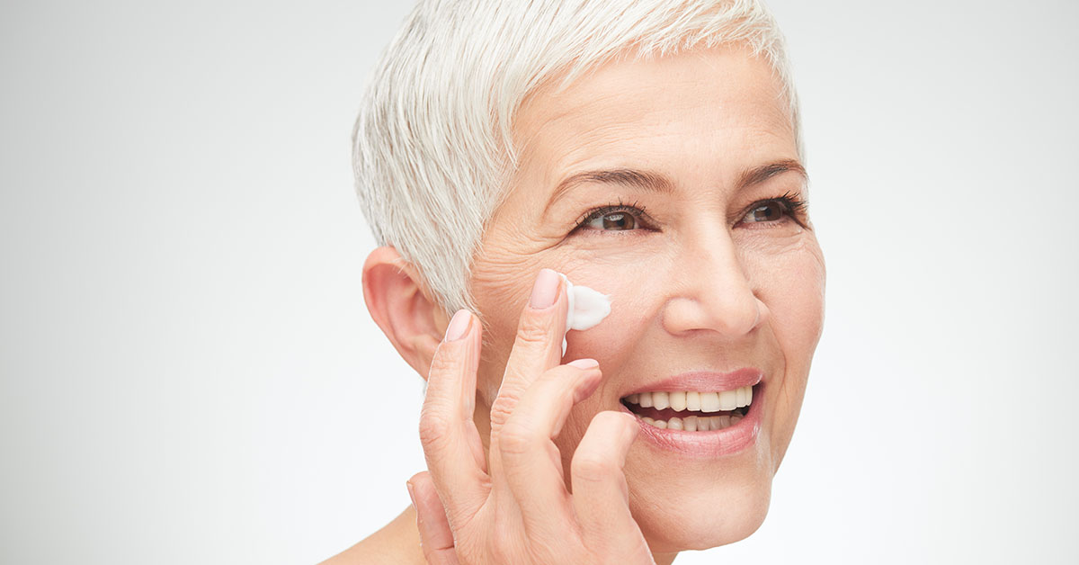 Head shot of beautiful senior woman putting on the cream; blog: 8 Menopause Skincare Tips