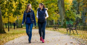 People walking in city park; blog: 10 Outdoor Fall Activities That Keep You Moving